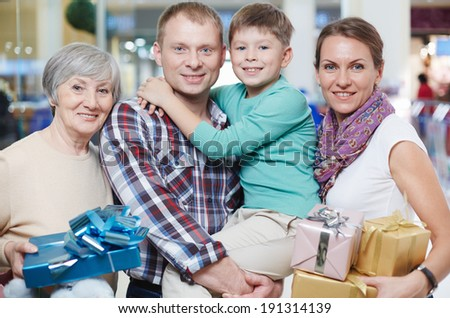 Portrait of happy family looking at camera in the mall - stock photo