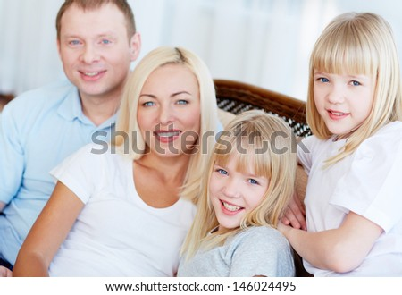 Portrait of happy family looking at camera with twin daughters in front