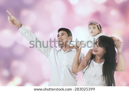 Portrait of happy family looking at copy space together, shot against blurred background - stock photo