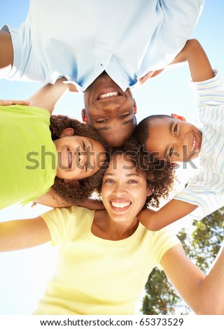 Portrait of Happy Family Looking Down Into Camera In Park