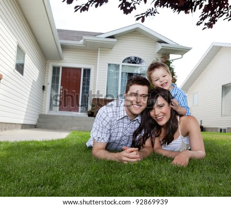 Portrait of happy family lying down on grass in front of house - stock photo