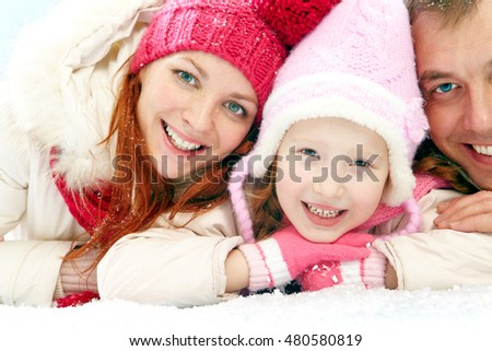 Portrait of happy family lying on snow and looking at camera
