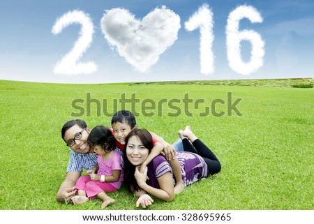 Portrait of happy family lying on the field and smiling at the camera with cloud shaped numbers 2016 - stock photo
