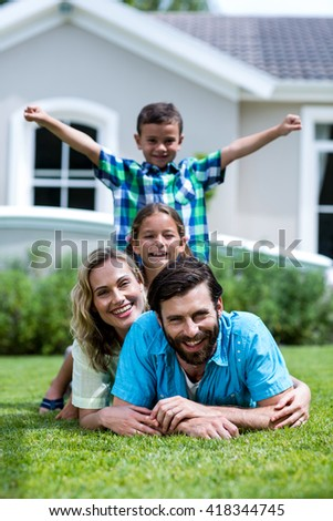 Portrait of happy family lying on top of each other over grass in yard - stock photo