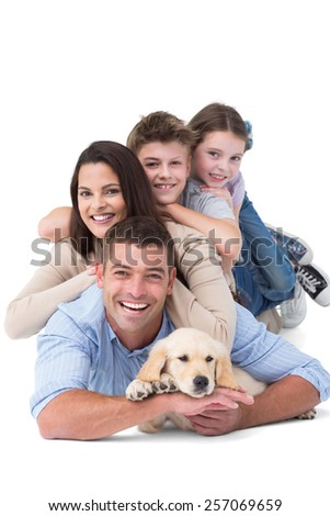 Portrait of happy family lying on top of each other with dog over white background - stock photo