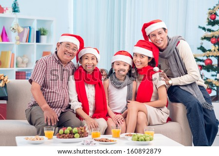 Portrait of happy family members in Santa caps sitting by Christmas table - stock photo
