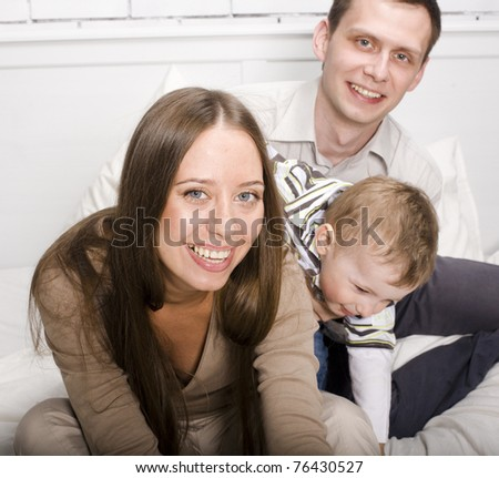 portrait of happy family, mom and dad playing with their son in bed - stock photo