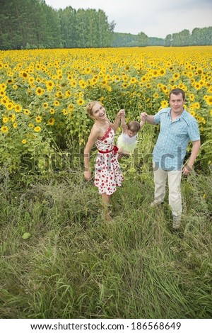 Portrait of happy family mom dad and daughter rocking her baby in her arms and having fun in the field of sunflowers Father and mother watching something up in sky outdoor shot - stock photo