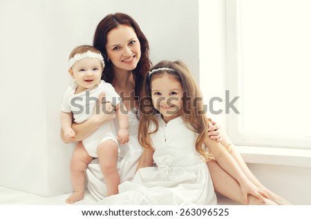 Portrait of happy family, mother together with two children at home in white room near window - stock photo