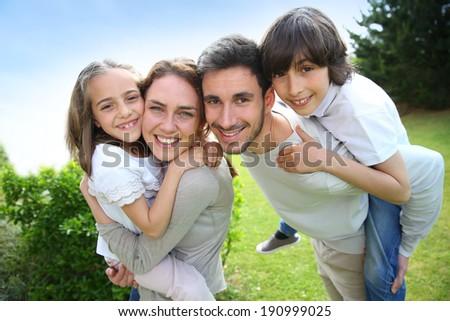 Portrait of happy family of four - stock photo