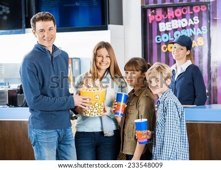 Portrait of happy family of four holding snacks while female worker standing at cinema concession stand - stock photo