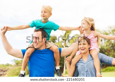 Portrait of Happy Family of Four Outside Playing - stock photo