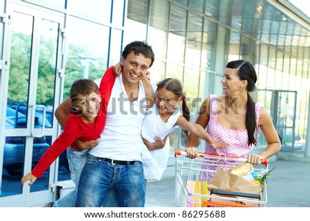 Portrait of happy family of four with cart of foodstuff - stock photo