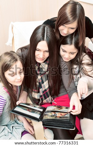 Portrait of happy family of only girls having fun together at their apartment. Looking their photo album - stock photo