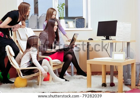 Portrait of happy family of only girls of different ages. They are looking at laptop display together - stock photo