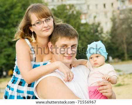 portrait of  happy family of three at city park - stock photo