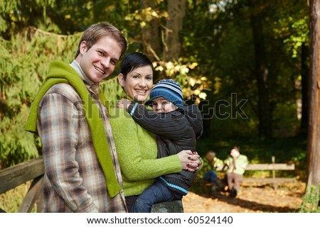 Portrait of happy family of three smiling at camera on autumn hiking.?