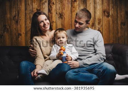 Portrait of happy family on sofa - stock photo