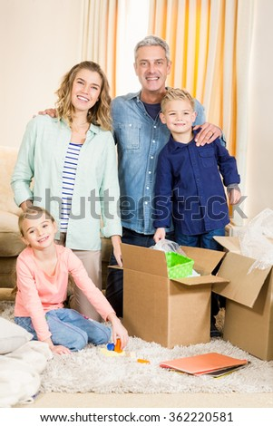 Portrait of happy family opening boxes in living room