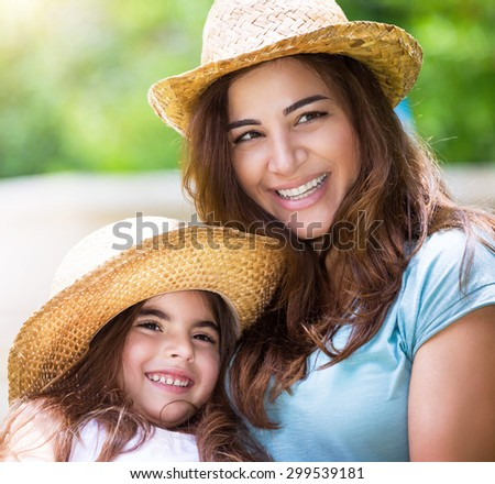 Portrait of happy family outdoors, cute cheerful mother with little daughter wearing identical straw hats and having fun on backyard - stock photo