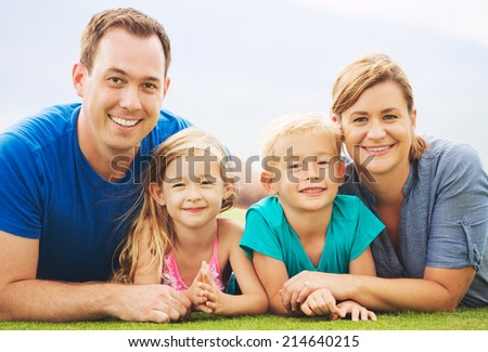 Portrait of Happy Family Outside on Grass - stock photo