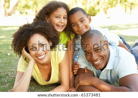 Portrait of Happy Family Piled Up In Park - stock photo