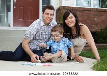 Portrait of happy family playing outside house on sidewalk - stock photo
