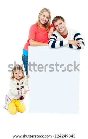 Portrait of happy family presenting blank whiteboard. Studio shot