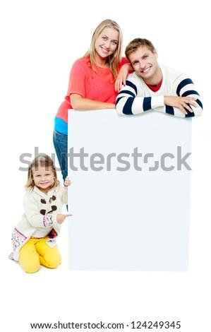Portrait of happy family presenting blank whiteboard. Studio shot - stock photo