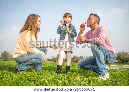 Portrait of happy family - Pretty young girl playing with soap bubbles in a park with her parents - stock photo