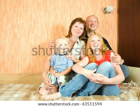 Portrait of happy family relaxing together indoor - stock photo