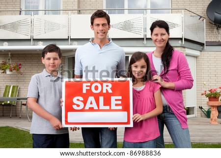 Portrait of happy family selling their home holding for sale sign board