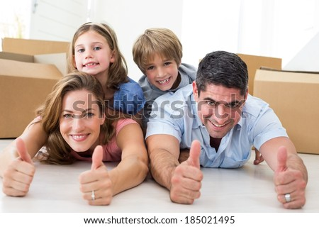 Portrait of happy family showing thumbs up sign while lying in their new house - stock photo