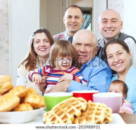 Portrait of  happy family sits on sofa in livingroom at home - stock photo