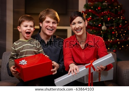 Portrait of happy family sitting at couch, holding christmas gifts, laughing.? - stock photo