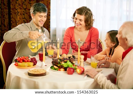 Portrait of happy family sitting at festive table and having Thanksgiving dinner - stock photo