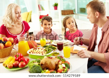 Portrait of happy family sitting at festive table and holding each other by hands before praying - stock photo
