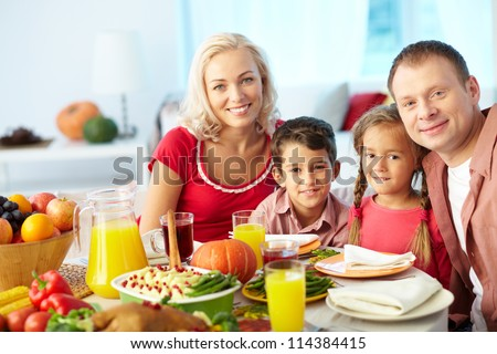 Portrait of happy family sitting at festive table and looking at camera - stock photo