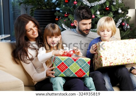 Portrait of happy family sitting at living room next to christmas tree while cute children holing in their hands christmas gifts.  - stock photo