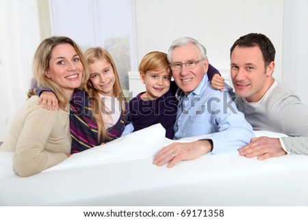 Portrait of happy family sitting in sofa at home - stock photo