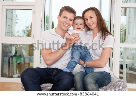 Portrait of happy family sitting on couch at home - stock photo
