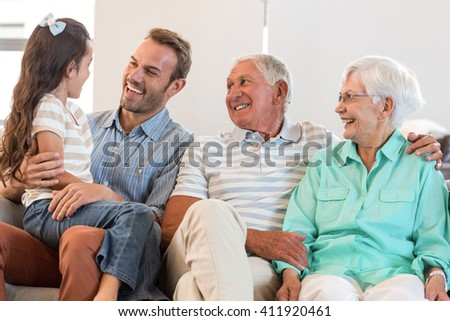 Portrait of happy family sitting on sofa in their living room - stock photo