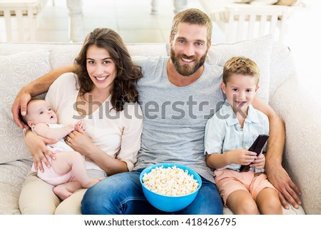 Portrait of happy family sitting on sofa watching television in living room - stock photo
