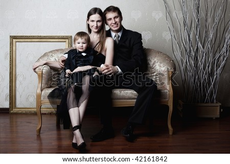 portrait of happy family sitting on the couch - stock photo