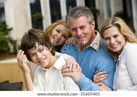 Portrait of happy family sitting poolside on patio - stock photo