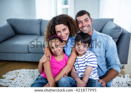 Portrait of happy family sitting together on floor in living room - stock photo