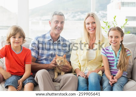 Portrait of happy family sitting with cat on sofa at home - stock photo