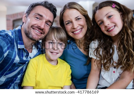 Portrait of happy family smiling at home - stock photo