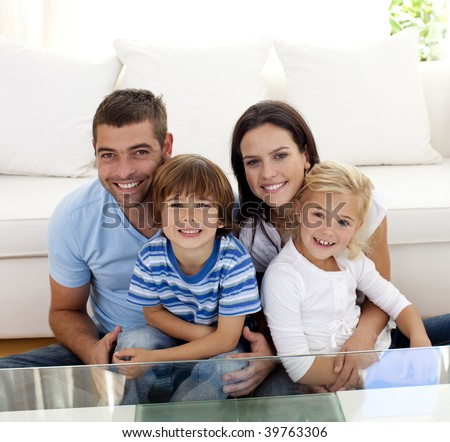 Portrait of happy family smiling at the camera in living-room - stock photo