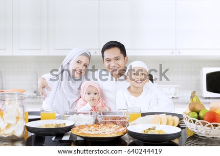 Portrait of happy family smiling together in the kitchen while sitting in front of dining table